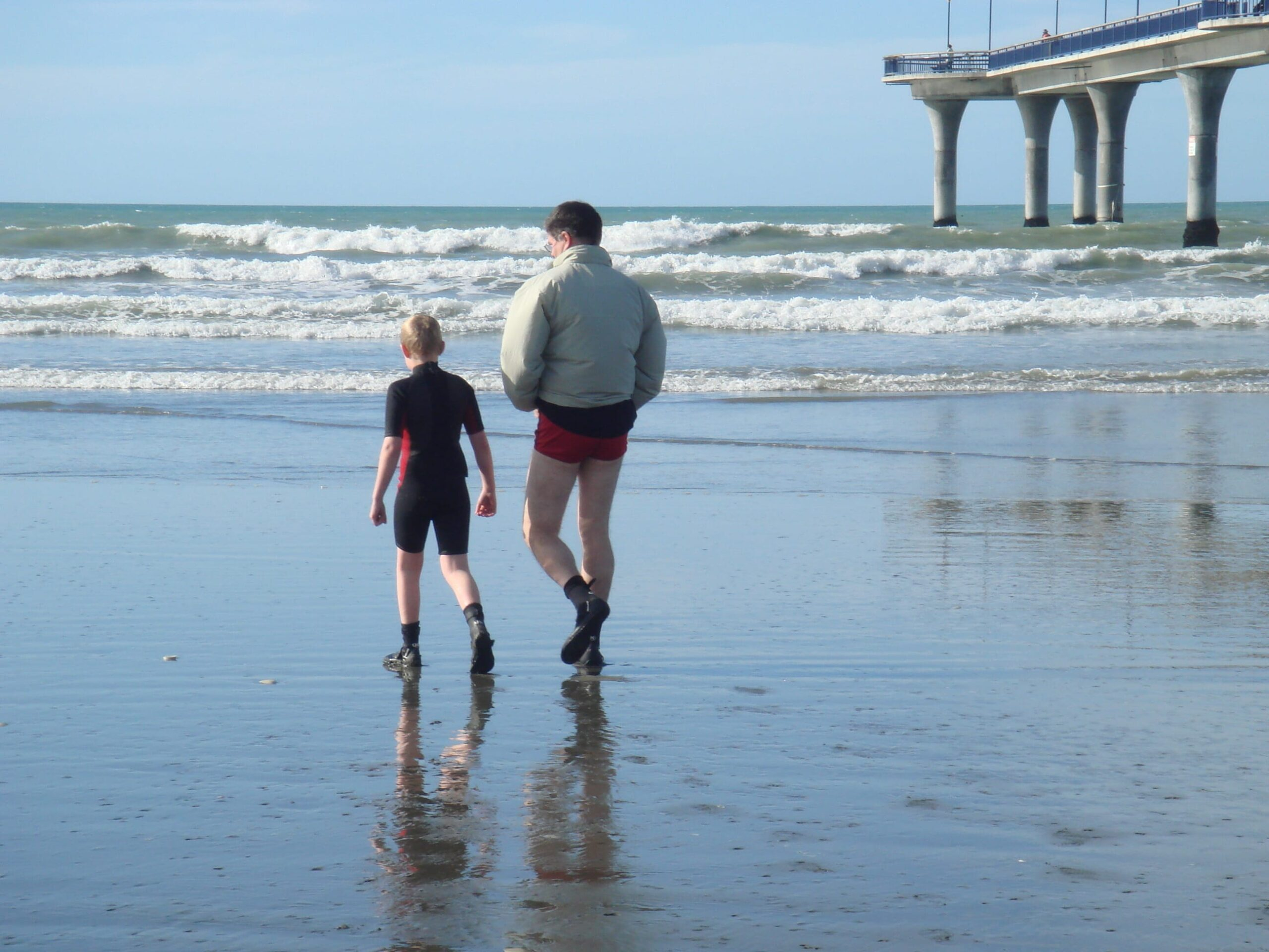 Grant and Mark walk on beach to open water surf in New Brighton, NZ